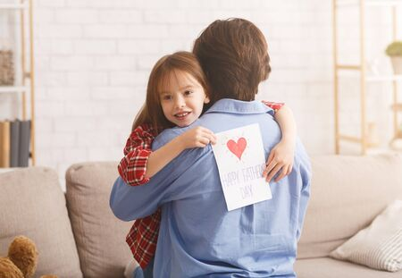 Cute little girl hugging her dad, holding greeting card, celebrating Father Day at home, empty space Banque d'images