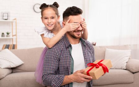 Fathers day surprise. Playful daughter surprising her dad, closing his eyes and giving gift at home, empty space