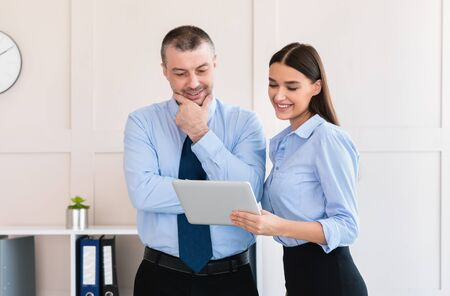 Businesswoman Showing Tablet Computer To Colleague Businessman Standing In Modern Office. Corporate Lifestyle Concept Zdjęcie Seryjne