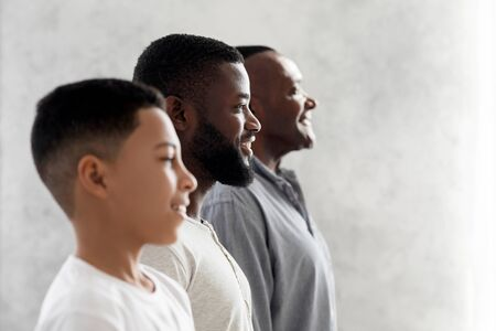 Multi Generational Male Family Portrait. Side View Of African American Son, Father And Grandfather Standing In A Row