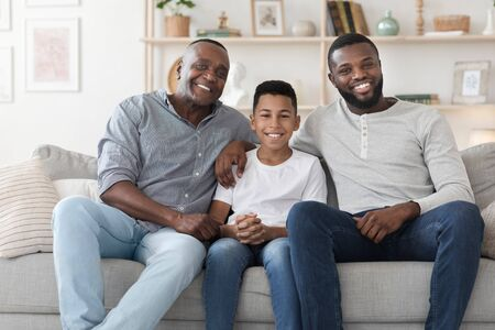 Multi generation male family members posing together at home, smiling to camera while relaxing on couch in living room