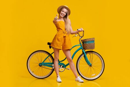 Eco Transport. Pretty Teen Girl Standing Next To Vintage Bike And Showing Thumb Up, Posing Over Yellow Background In Studio, Free Space