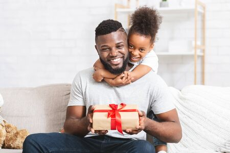 Loving black little girl giving gift to her dad, Fathers Day concept