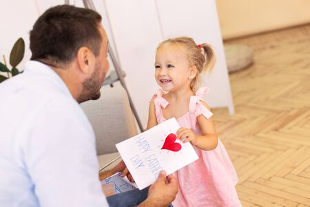 Love You. Daughter congratulating dad and giving him postcard with Happy fathers day text, free space Banque d'images