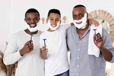 Three generational men family shaving together in bathroom and smiling at camera, posing with razors in hands and with foam on faces