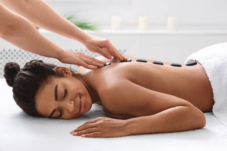 Therapist hands and young african woman enjoying hot stones massage, spa day concept