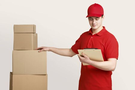 Postman in uniform at warehouse checks for presence of all parcels, holding tablet in hands, isolated on light background, studio shot
