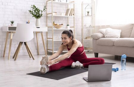 Female yoga instructor running online training session via laptop at home