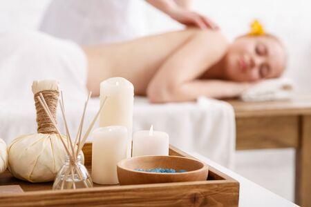 Massage ayurvédique. Sel, bougies, bâtons aromatiques et sacs aux herbes, gros plan, professionnel faisant un massage à une fille sur table Banque d'images
