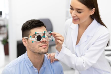 Eyesight Test Concept. Beautiful female optometrist checking patients vision with trial frame, one eye closed Foto de archivo