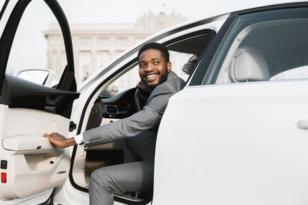 Car Rental. African American Businessman Opening Automobile Door Getting Out Of Auto In City.