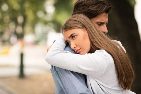 Stuck In Relationship. Unhappy Girl Hugging Unloved Boyfriend Standing Outdoors In Park. Free Space For Text