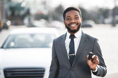 New Car. Joyful Black Businessman Showing New Automobile Key Standing Near Luxury Auto In City. Free Space Stok Fotoğraf