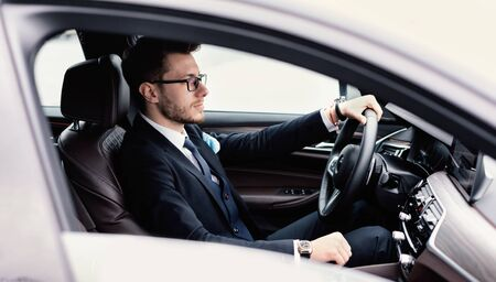 Confident Businessman Concept. Young man in glasses driving in luxury car, side view Stok Fotoğraf