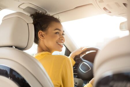Own Car. Cheerful Black Woman Driving Auto Sitting In Drivers Seat In Automobile. Back View, Selective Focus