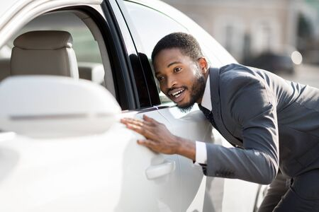 New Car Concept. Black Businessman Checking And Touching His New Automobile In Excitement Outside. Selective Focus, Copy Space Stok Fotoğraf