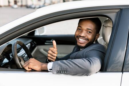Great Car. Smiling African Businessman Gesturing Thumbs Up Sitting In Drivers Seat After Test Drive. Selective Focus Stock Photo