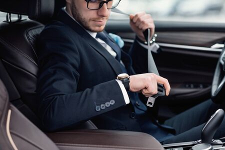 Fasten Your Seatbelt. Bearded Man Wearing Glasses And Wristwatch Putting On Safety Strap Sitting In Luxury Car