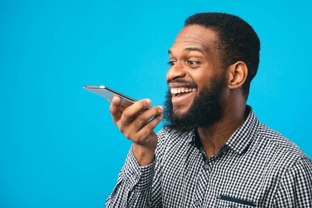 Happy young black man using voice assistant on smartphone, isolated over blue studio wall, copyspace