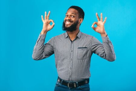Im Fine. Close up portrait of happy african business man doing ok gesture isolated over blue studio wall, copyspace