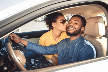 New Car Owners. Black Wife Kissing Happy Husband Sitting In New Luxury Auto. Selective Focus