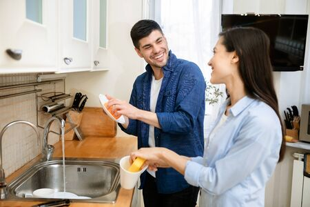 Togetherness Concept. Portrait of young lovely family washing dishes, laughing and looking at each other