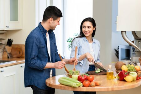 Healthy Food At Home. Happy loving couple is preparing the proper meal in modern kitchen in their apartment