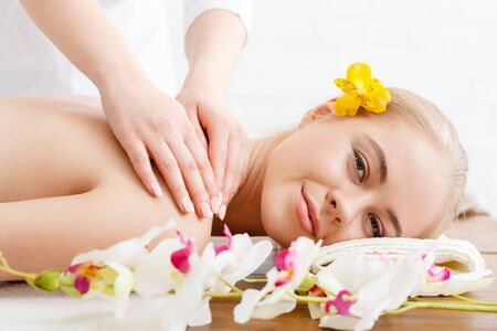 Relaxing in spa. Smiling girl lies on massage table, female hands massage shoulders, close up, free space