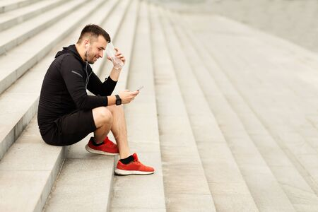 Side view portrait of young sportsman having a break from exercising, holding bottle of mineral water, using cell phone