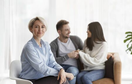 Professional Marital Therapist Smiling To Camera While Her Clients Reconciling After Successful Therapy Sitting On Couch In Office. Selective Focus Foto de archivo