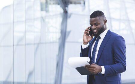 Communication d'entreprise. Joyeux homme d'affaires africain parlant sur téléphone portable négociant un accord debout dans une zone urbaine à l'extérieur. Espace de copie