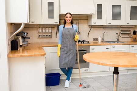 Ready For Cleaning. Satisfied caucasian woman standing in kitchen, posing with mop, full length, copyspace