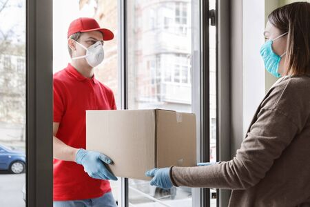 Stay home concept. Courier in protective mask and gloves gives parcel to girl in self-isolation
