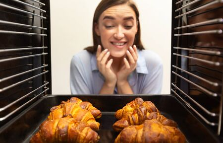 Homemade baking. Glad girl looking at tasty fresh croissants, view from inside of oven