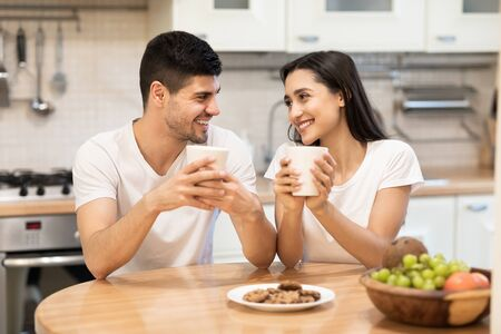 Morning Coffee. Happy couple holding mugs with hot beverage after breakfast, sitting at table, looking at each other Imagens