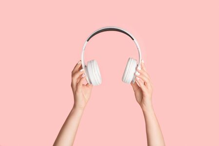 Cropped view of millennial girl holding headphones on pink background