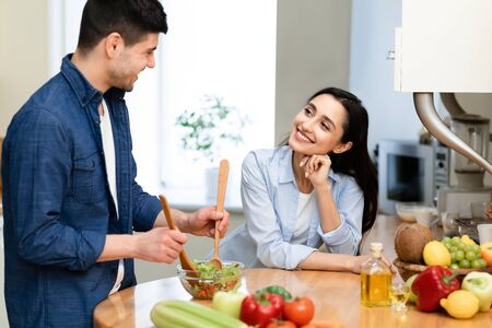 Lifestyle Concept. Young man cooking healthy meal in modern kitchen, cute girl looking and listening to him Imagens