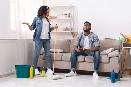 Household Chores Problem. Displeased African Woman Blaming Her Lazy Husband Playing Video Games While She Cleaning