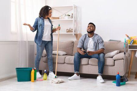 Problème de tâches ménagères. Une femme africaine mécontente accuse son mari paresseux de jouer à des jeux vidéo pendant qu'elle nettoie