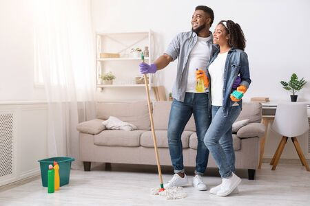 Happy Black Couple Standing In Fresh-Cleaned Living Room And Looking Aside, Satisfied After Successful Tidying, Copy Space