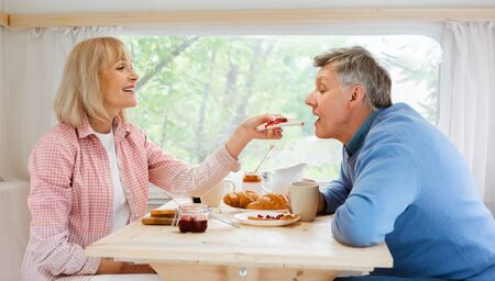 Camping trip together. Beautiful mature woman feeding toast with jam to her husband inside of their motorhome