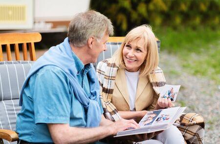 Senior couple looking through their family photo album near RV on camping site 免版税图像
