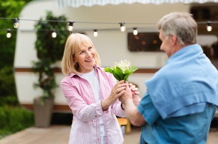 Senior man giving bouquet of flowers to his beloved wife near camper van outdoors