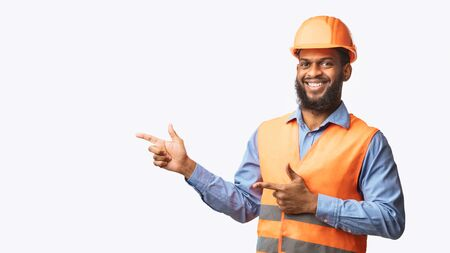 Smiling African Builder Guy In Uniform Pointing Fingers Aside At Free Space Standing On White Studio Background. Panorama