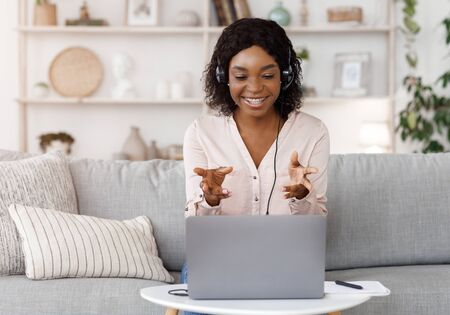 Online Tutoring Concept. Smiling black female tutor having video call with student, giving language class by webcam, sitting on couch at home