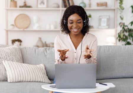 Concept de tutorat en ligne. Tutrice noire souriante ayant un appel vidéo avec un étudiant, donnant un cours de langue par webcam, assise sur un canapé à la maison