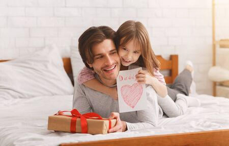 Lovely preschool girl greeting her happy daddy with Father Day, giving him gift box and greeting card, laying on bed together at home, free space