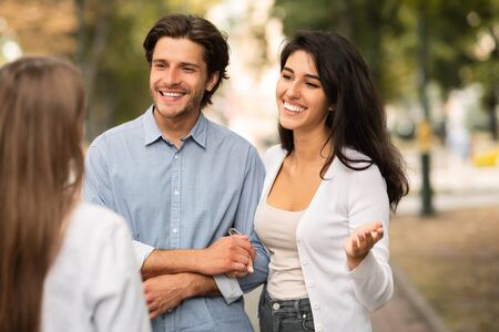 Married Couple Meeting Single Female Friend Walking Outdoor In Park. Friendship With Ex-Boyfriend Concept. Selective Focus Stock Photo
