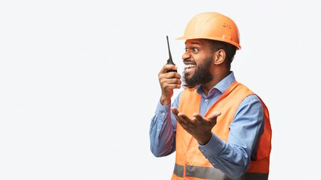 Mad african construction site supervisor yelling in two-way radio standing on white studio background. Building industry concept. Panorama, free space Banco de Imagens