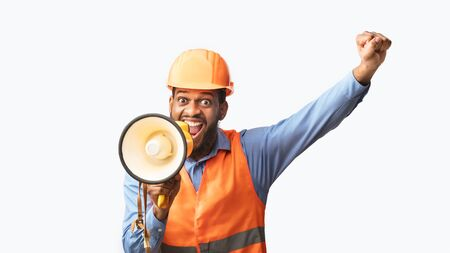 Excited African American Builder Worker Shouting In Megaphone Announcing Great Building News Standing On White Studio Background. Panorama